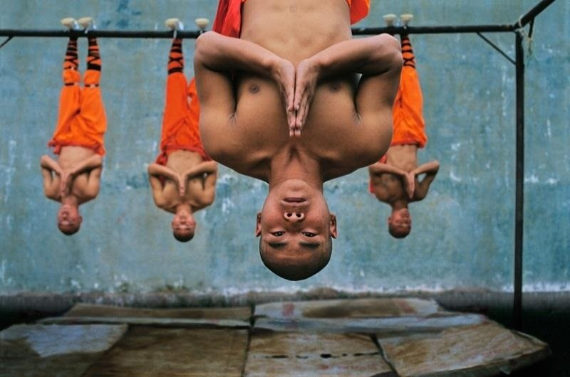 group of monks hanging upside down meditating