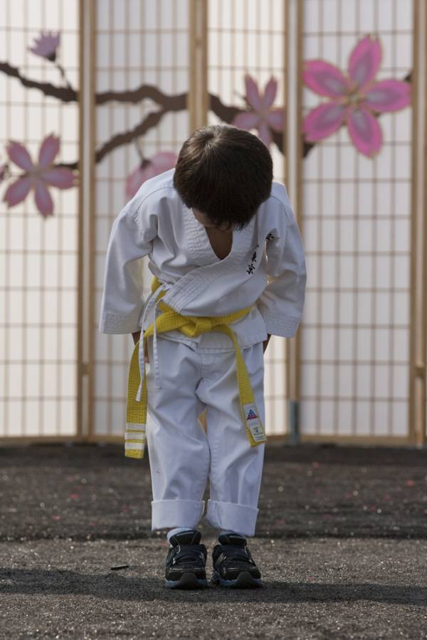 young martial artist in uniform bowing